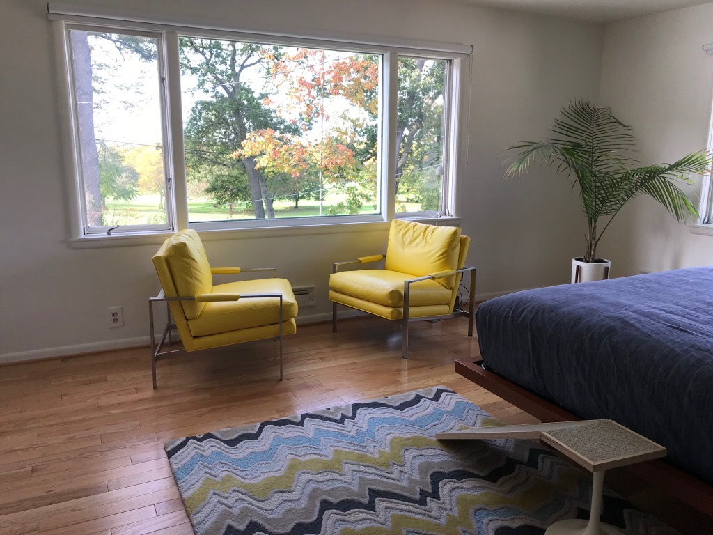 MASTER BEDROOM WITH YELLOW CHAIRS AND VIEW OF SUNSET OVER GOLF CLUB