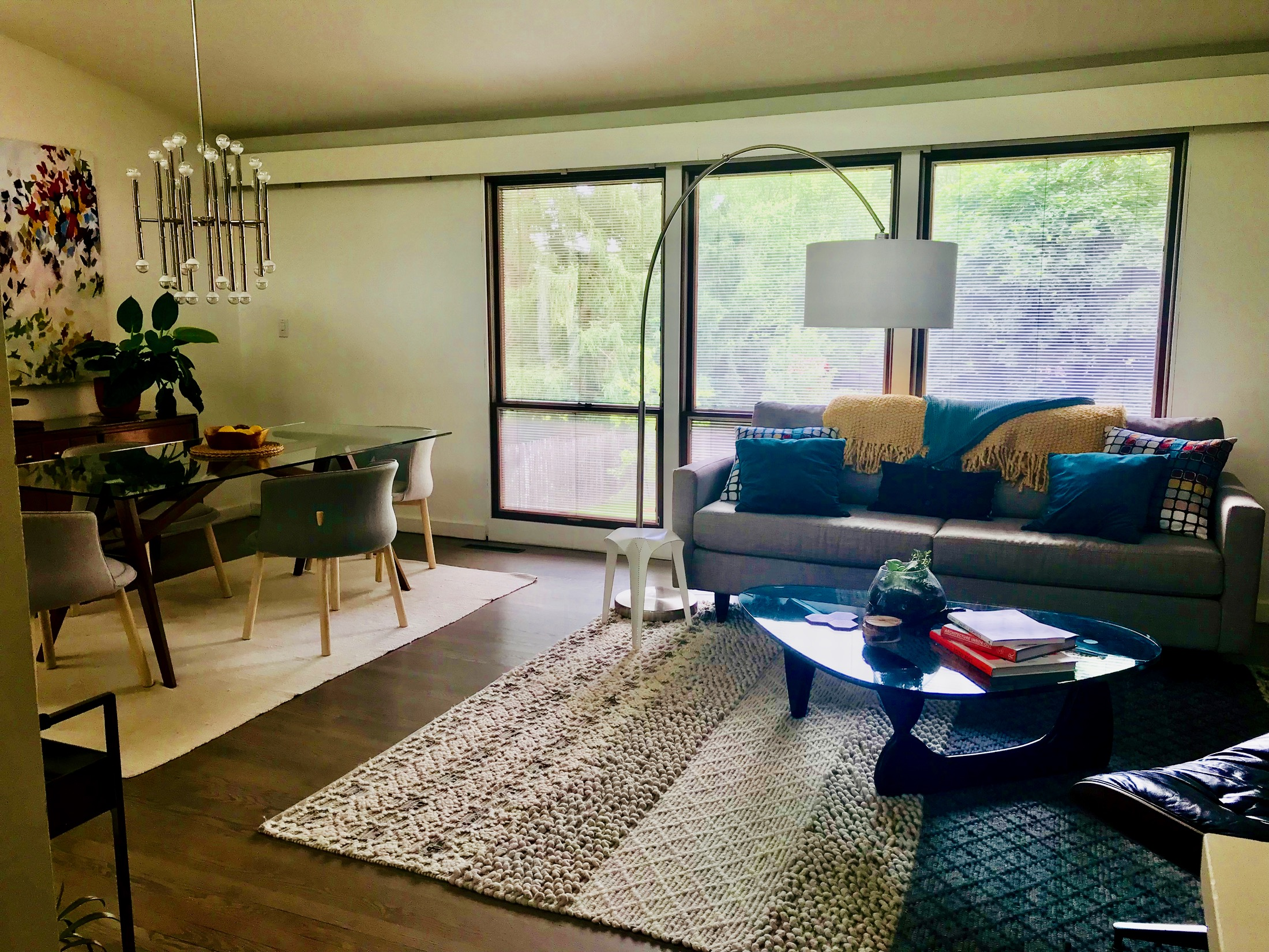 Open concept living room - dining area with large three part windows overlooking the backyard.