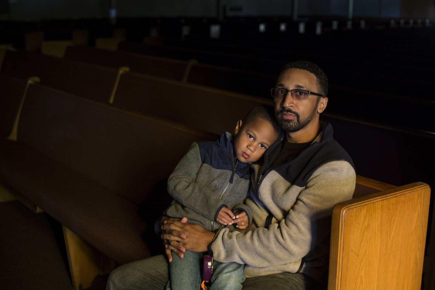 The Rev. Rigel Dawson, who leads North Central Church of Christ in Flint, took on the responsibility of distributing bottled water to his congregation. With him is his son, Roman. (Brittany Greeson/The Washington Post)