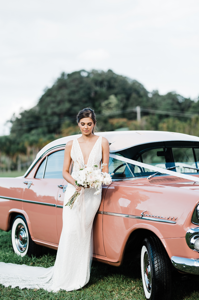 A Rosy Pink Vintage Dream Machine - Meet May the E.K., a rosy pink 1962 EK Holden Special Sedan and the cherry on top of your special day. This vintage dream machine is available for hire in the Byron Bay area for couples who favour timeless glamour and a memorable exit. Forget the stuffy Rolls Royces of the past and opt for May's dusty rose and chrome highlights - we find it a much more romantic approach to transportation. Owned by fashion stylist Kirsten Butler, every detail has been carefully thought out and prepped for. You'll find an emergency fashion kit onboard, as well adorable pink handheld fans to keep you cool, and even a selfie stick for capturing those whirlwind moments! Visit WebsiteByron Bay, AustraliaPhone: +61 4 1513 6007Email: hello@maytheek.com