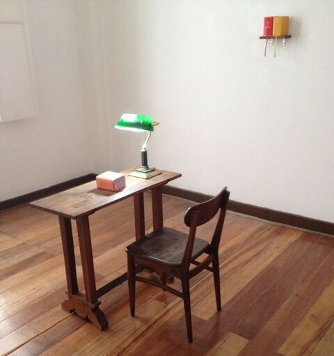 installation view: table: Peach Book of Slogans , 2014 shelf: Red Book of Slogans , 2008 and Yellow Book of Slogans , 2010