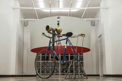 Installation view: front:  Hasa , 2015, modified bike, brass bells, wood | back:  Bell , 2013/2015, metal, paint, motor