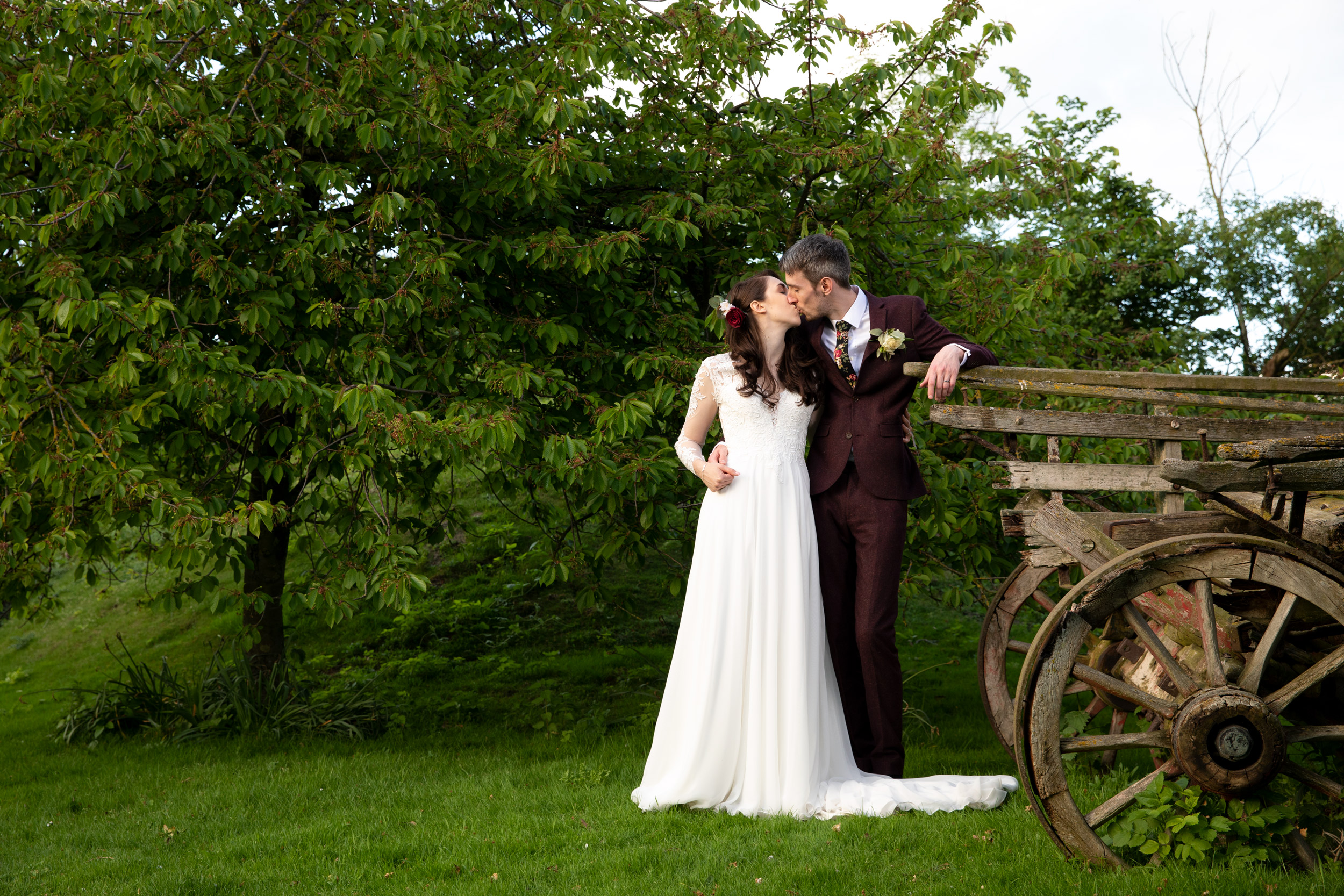 The Bride and Groom Steal a Kiss - Cooling Castle Barn - Kent Wedding Photographer