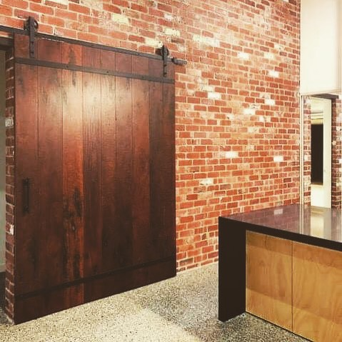 Feature red brick wall + timber door at a recently completed project.  #clarkeandcobuilders #design #quality