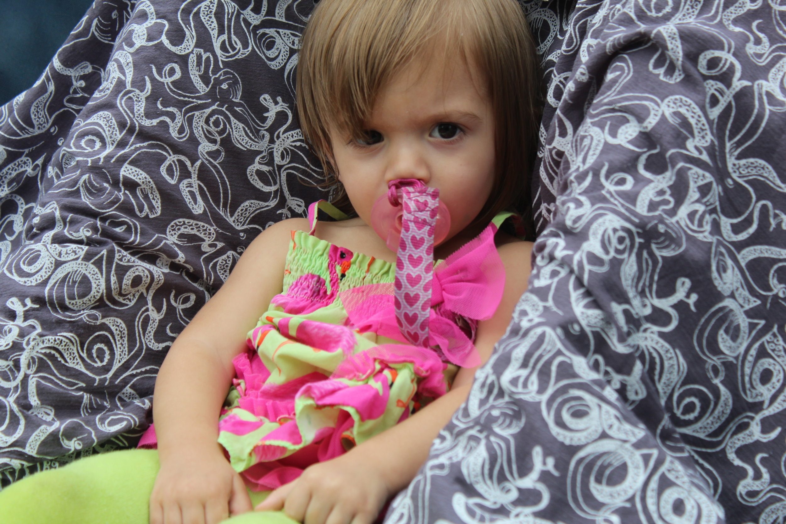 Sadie relaxing in the triple stroller. Pictured:  Swaddle Blanket