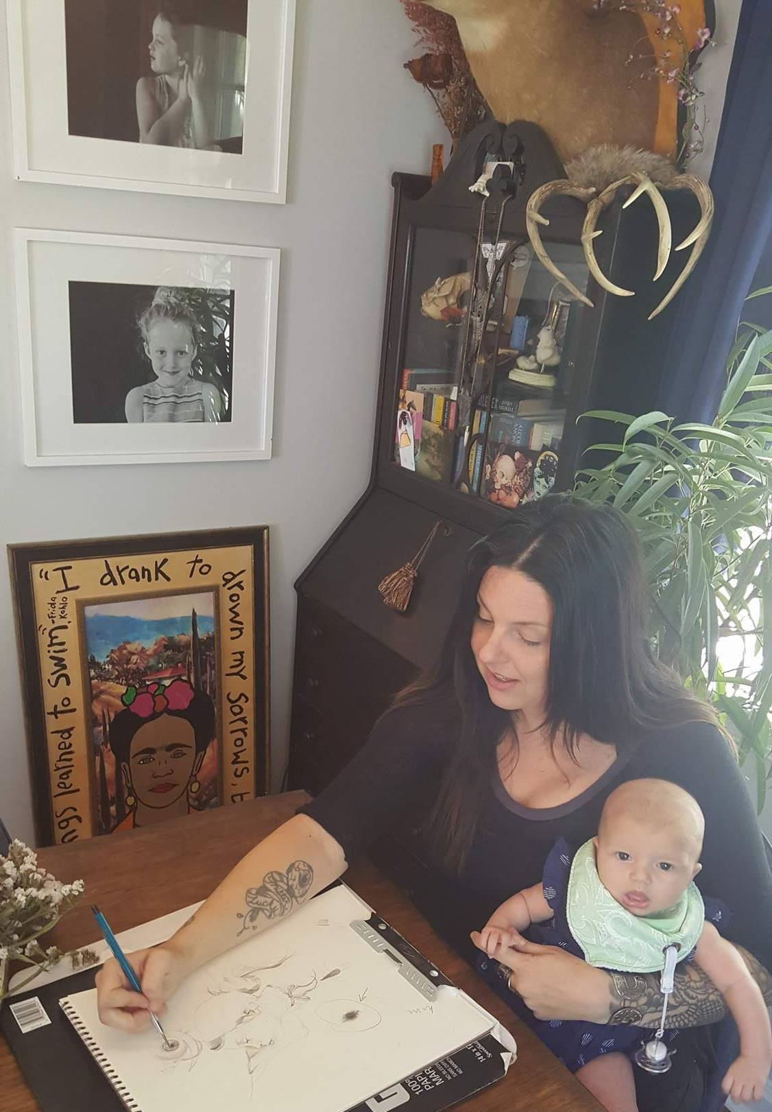 Kelley drawing a new piece with her youngest daughter in arm and two older daughters photos hung nearby on the wall.