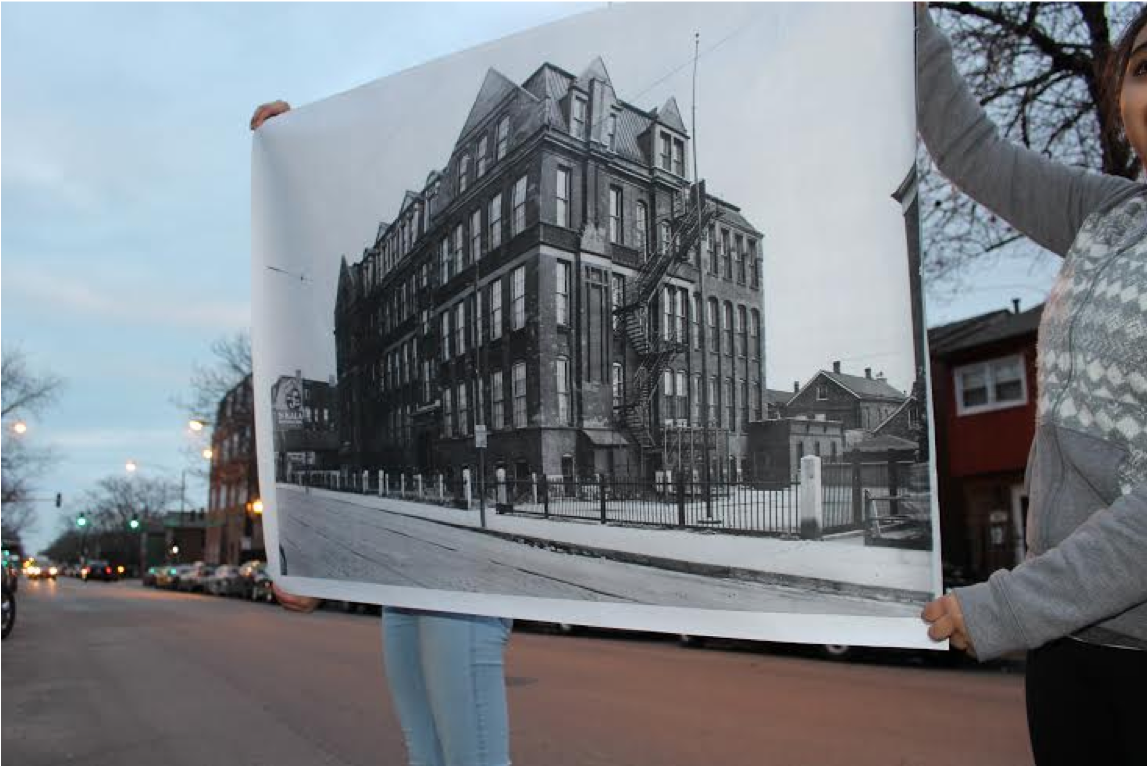students stand in the site where Froebel School once stood at 21st street and Damen, holding a large printed image of  the school