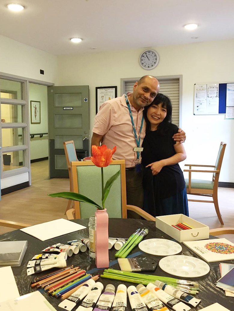 Reid with artist Yukako Shibata, as she prepares for a painting workshop for patients at Garnet Ward. Yukako transformed the ward's Sitting Area with a stunning wall painting, layering soft sunset colours to create a calming space for retreat.