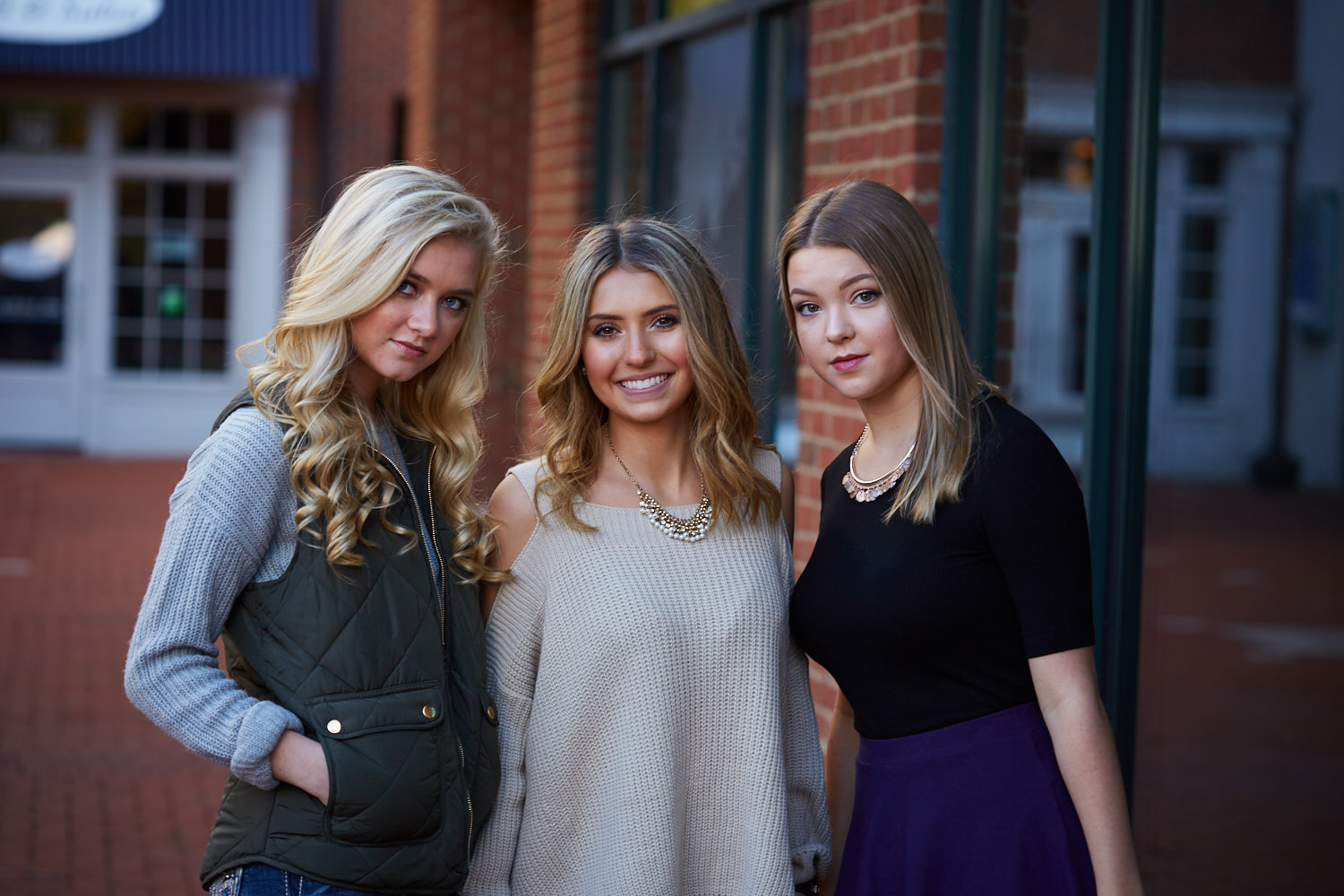 Three Senior girls pose in courtyard