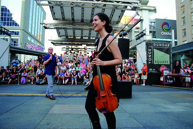 Carol Gimbel celebrating her production #1000Strings, a one-time only participatory performance of composer John Oswald's composition Spectre at Young-Dundas Square in Toronto.  Photo credit Sean Waisglass