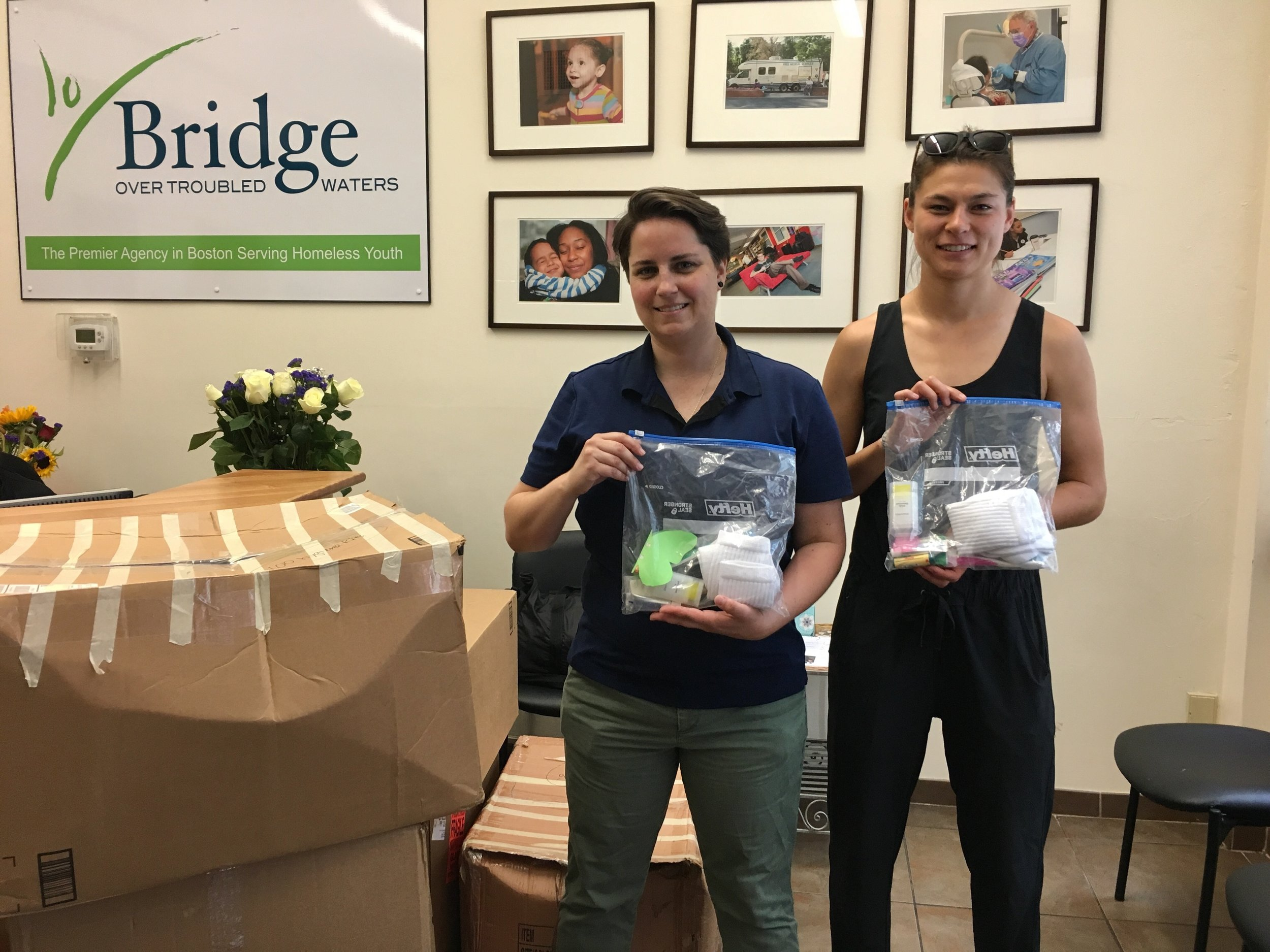A Bridge staff member poses with Erin Rea of Boston Cares with two of the toiletry kits.
