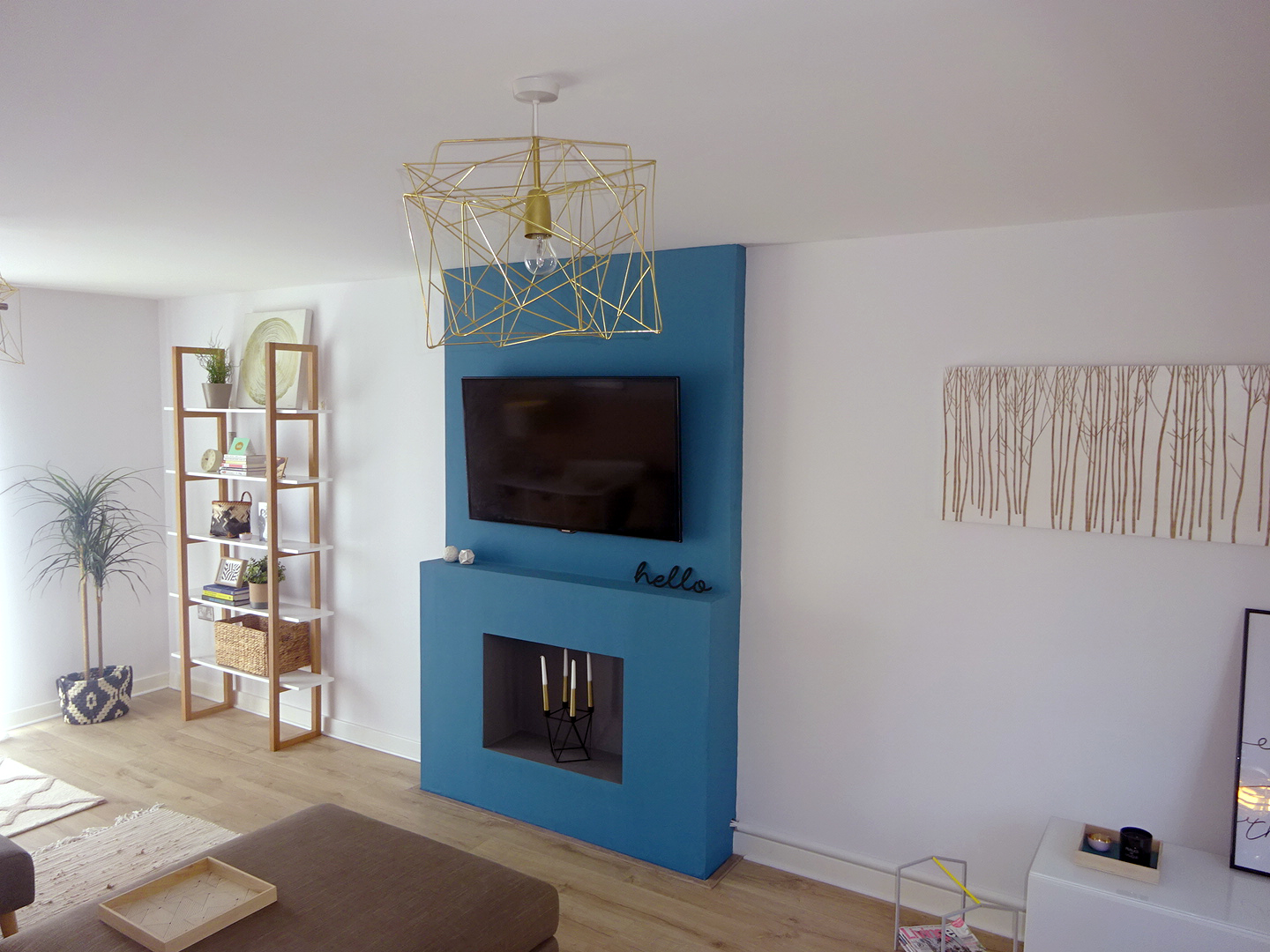The living room now has a focal point with the teal fire surround. All the accessories around it are brass, black/white or oak to complement it.