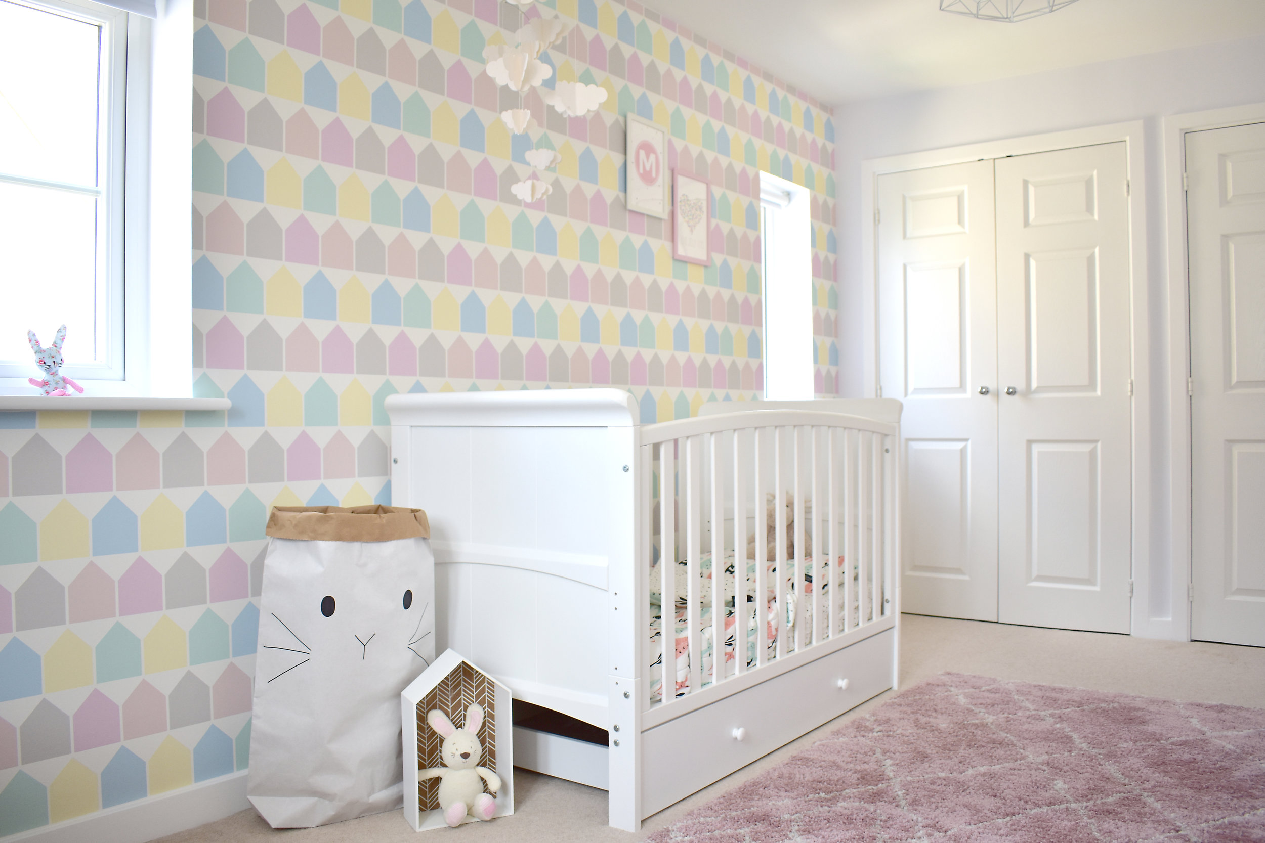 The  Beach Huts wallpaper  makes the feature wall and is the perfect soft contrast to the white of the furniture and walls