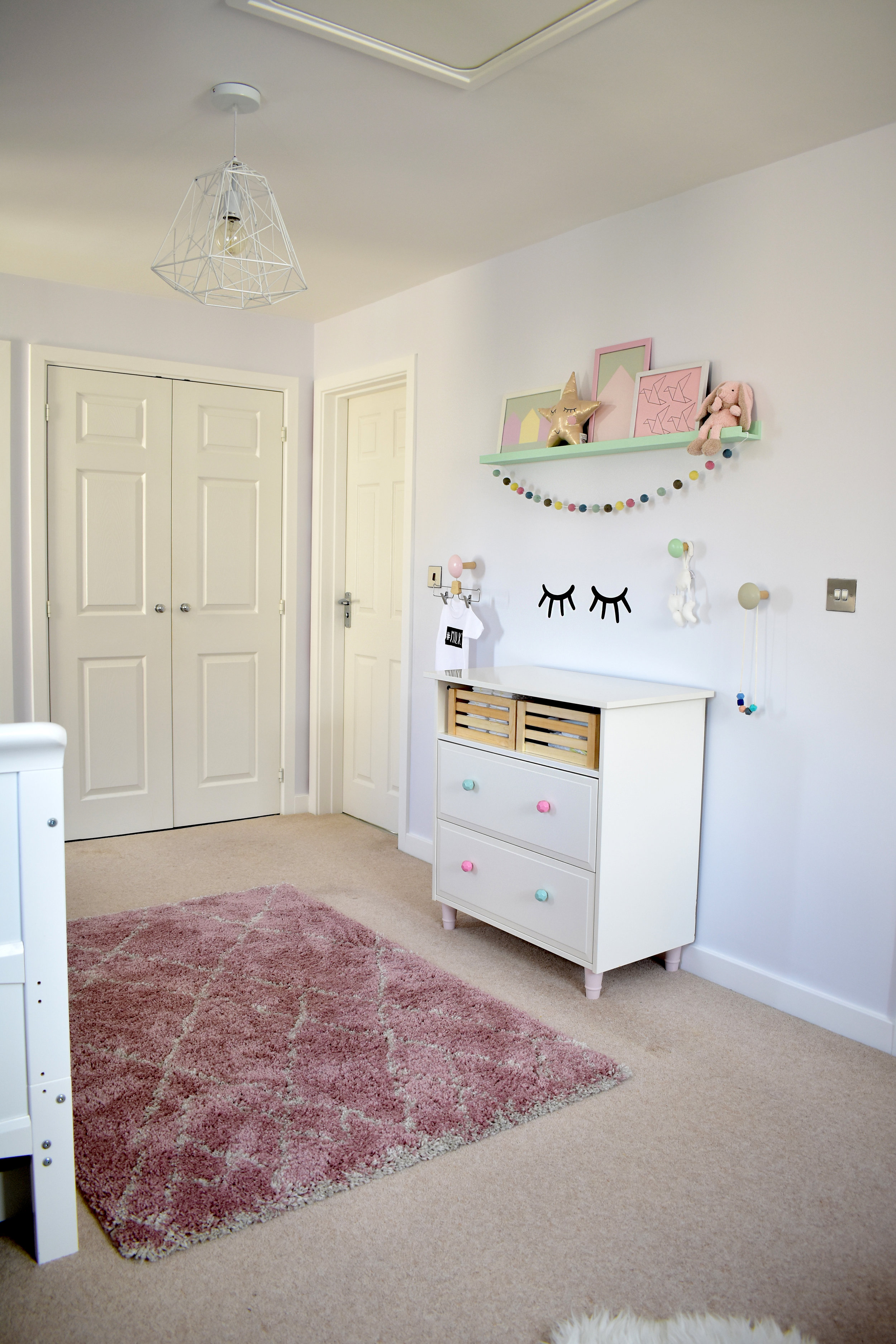 I use a chest of drawers as a changing unit, and created a sensory feature complete with the  Sleepy Eyes wall sticker  and a coloured  felt ball garland from Stone & Co.