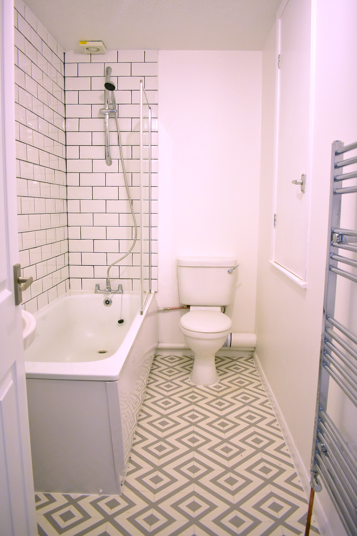 New tiles,vinyl flooring, and white paint made a world of difference in the bathroom