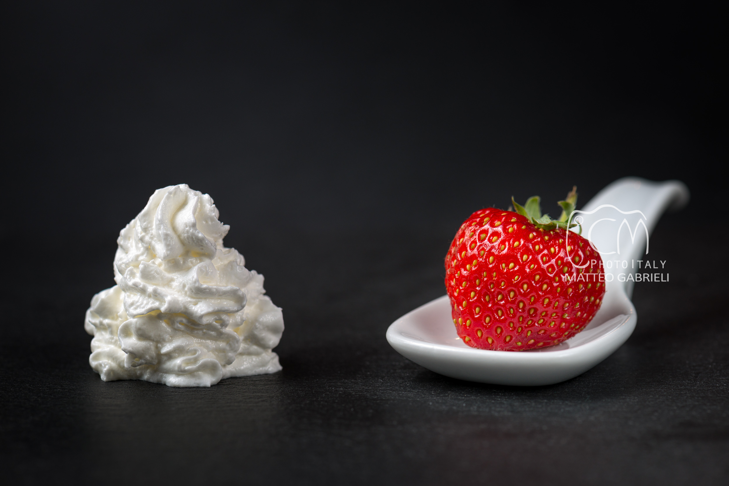The whipped cream meets the strawberry in the spoon, minimalist style food