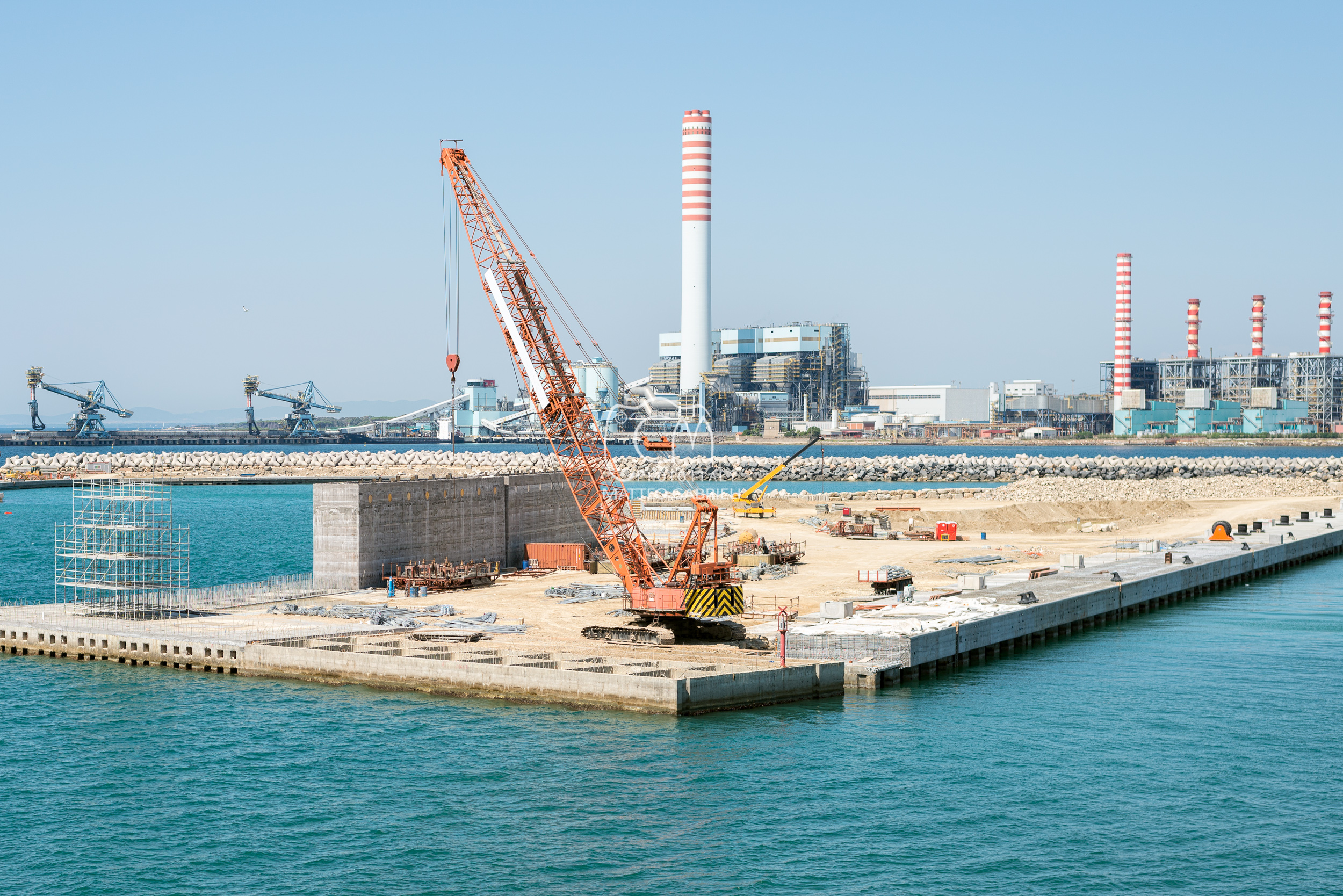 A Crane is building new harbour docks facing a thermal power plant, Civitavecchia Italy