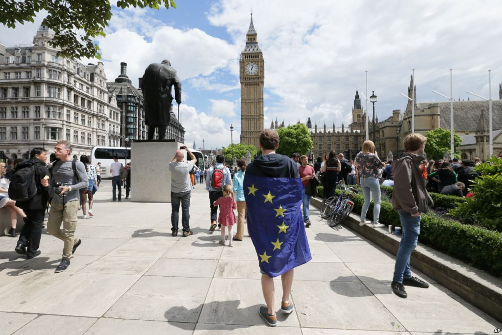 A demonstrator wrapped in the EU flag takes part in a protest opposing Britain's exit from the European Union in Parliament Square in London following the EU referendum result.  TIM IRELAND    The Associated Press