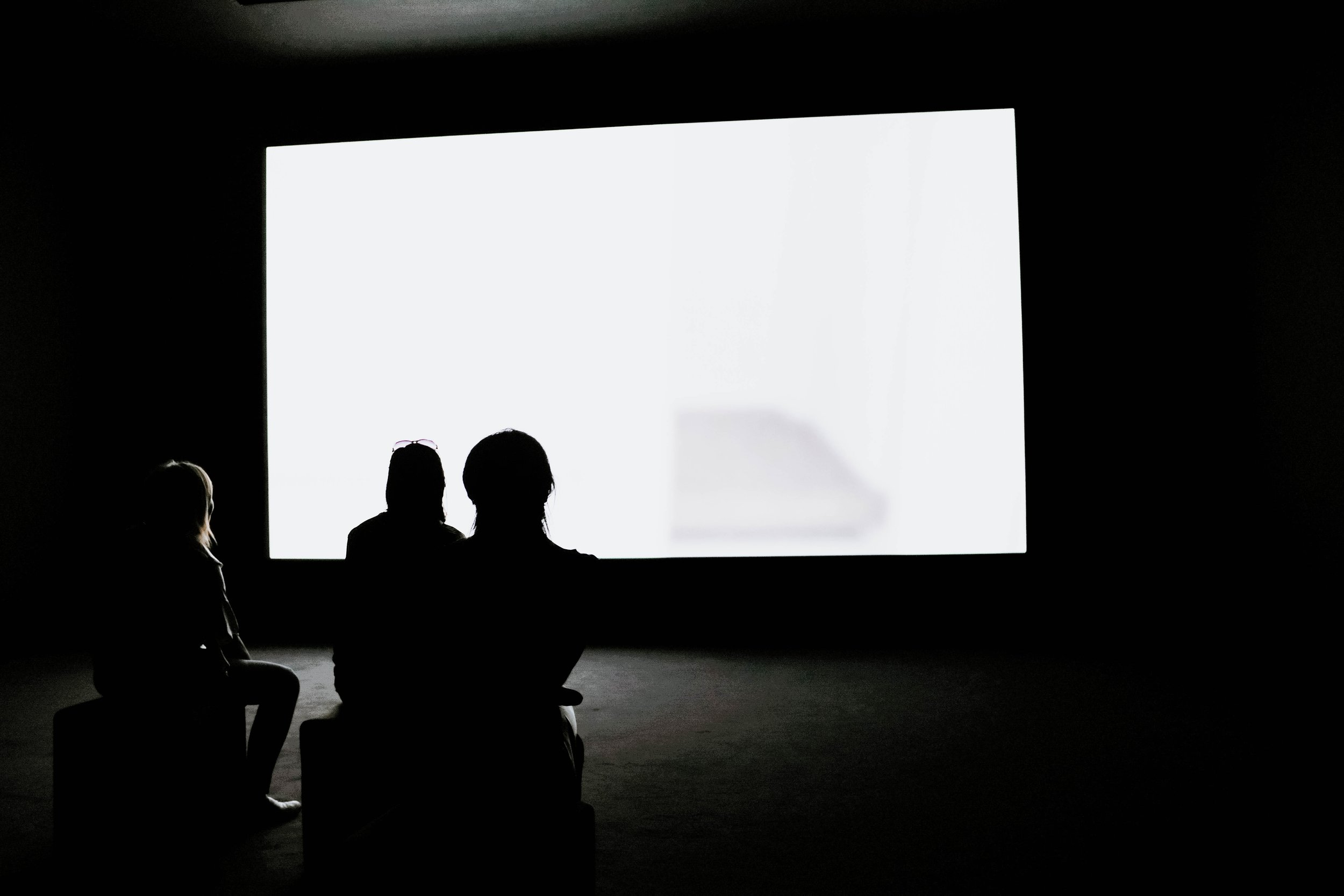 people looking at projection screen, parent with kids, black and white photo