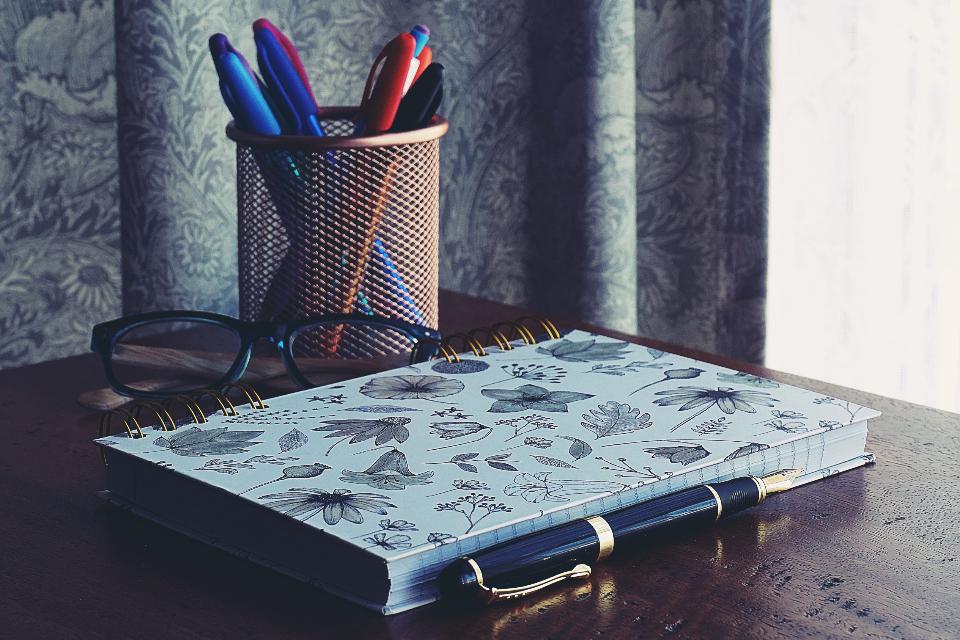 notebook on desk, glasses, workbook
