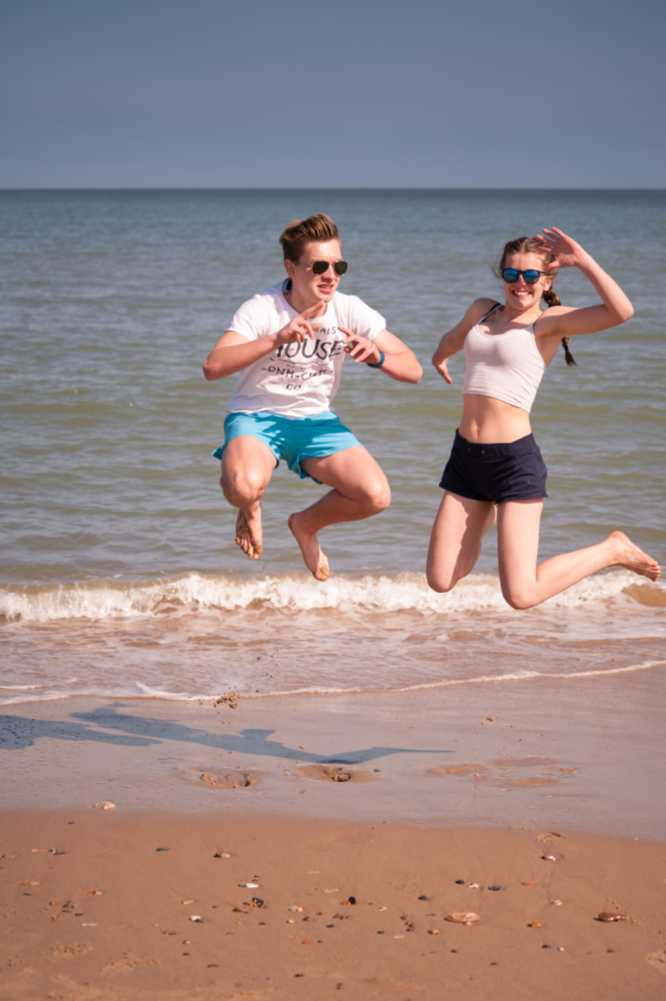 kids jumping at beach, teenagers, family vacation