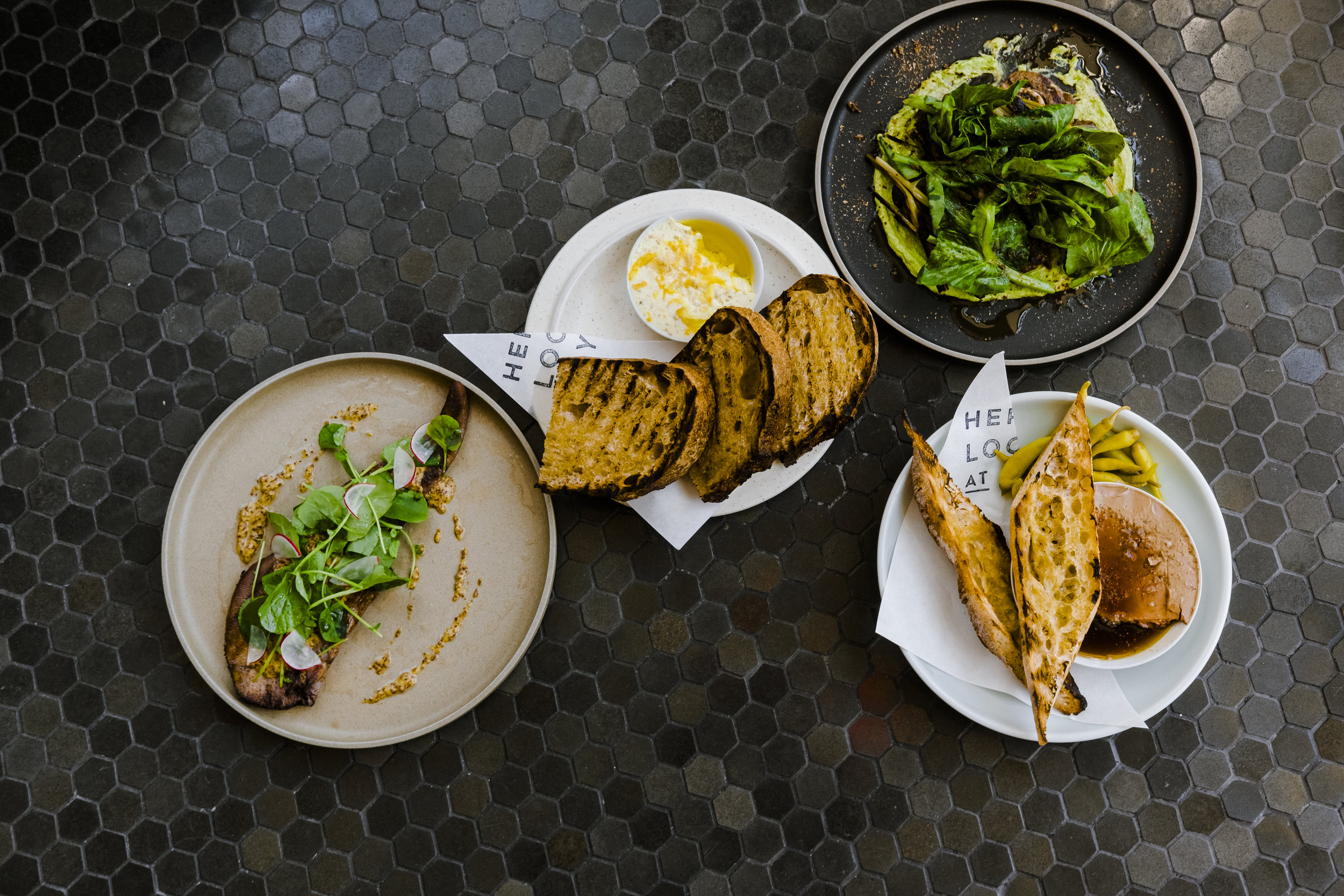 Image depicts Smoked beef tongue with garum mustard, cress, horseradish. Bub & grandma's bread with shiitake butter and sea salt. Lamb shoulder chop with miso, greens, minari, onion, and togarashi. And Chicken liver with basque peppers, smoked maple, and Bub & Grandma's baguette.
