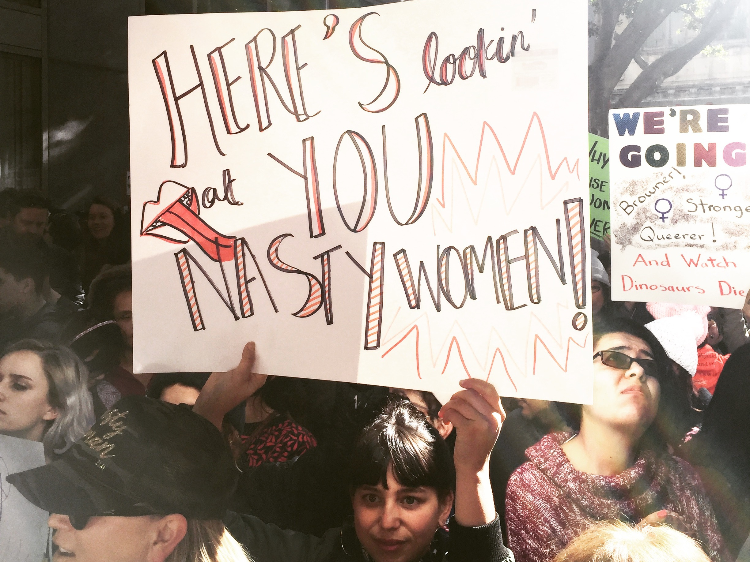 """Image depicts a photo of a young woman holding a sign depicting the words """"Here's lookin' at you NASTY WOMEN!"""" with a drawing of red lips and a tongue."""