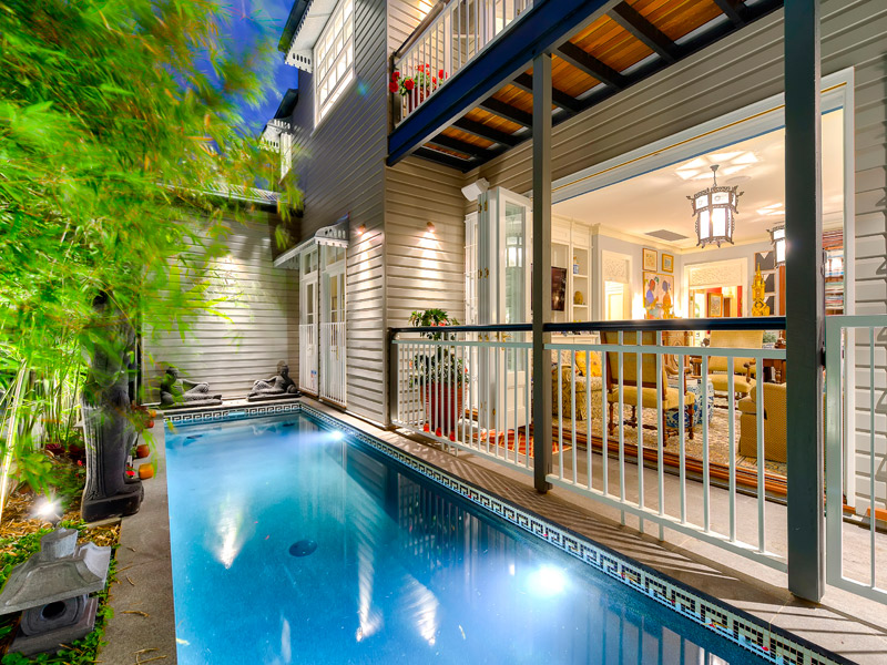 In Brisbane in Summer Months one would regard a swimming pool a necessity, rather than a luxury.On inner city blocks of land, one has to imagine sometimes how a pool can fit the building site, but one should also not be limited by something that may appear difficult. The above image was one such example of a difficult block of land, but with extensive renovations to the original house, it allowed easier access to the rear of the home for the pool to be constructed. The result is a pool that fits perfectly into the confined area, without overwhelming the house. The bifold doors of the downstairs Sitting Room, retract to allow a large open expanse overlooking the pool area, and Balinese inspired gardens. Allowing the interiors to be an extension to the outside area , which also creates the feeling of more space, internally and externally. A very successful integration, of using land, architecture and interiors to create the perfect inner city home.