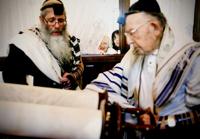 Lillian Croenwalt and Shainie Weingarten peek through a curtain dividing women and men to watch Croenwalt's husband, Lee, 90, read from the Torah with Rabbi Yisroel Wingarten (left) during his Bar Mitzvah Sunday, Dec. 25, 2011, at the Chabad House in Flint Township, Mich.