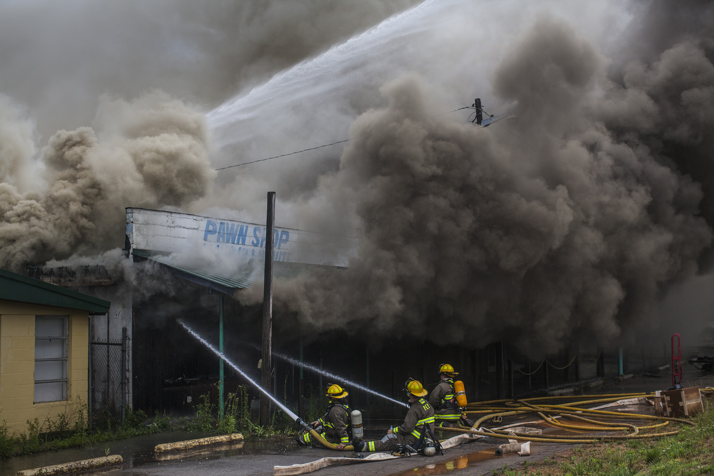 Firefighters from Portland, Tenn., and Franklin, Ky., work to put out a blaze at Dixie Discounts on Nashville Road on Thursday, May 12, 2016, in Franklin, Ky.