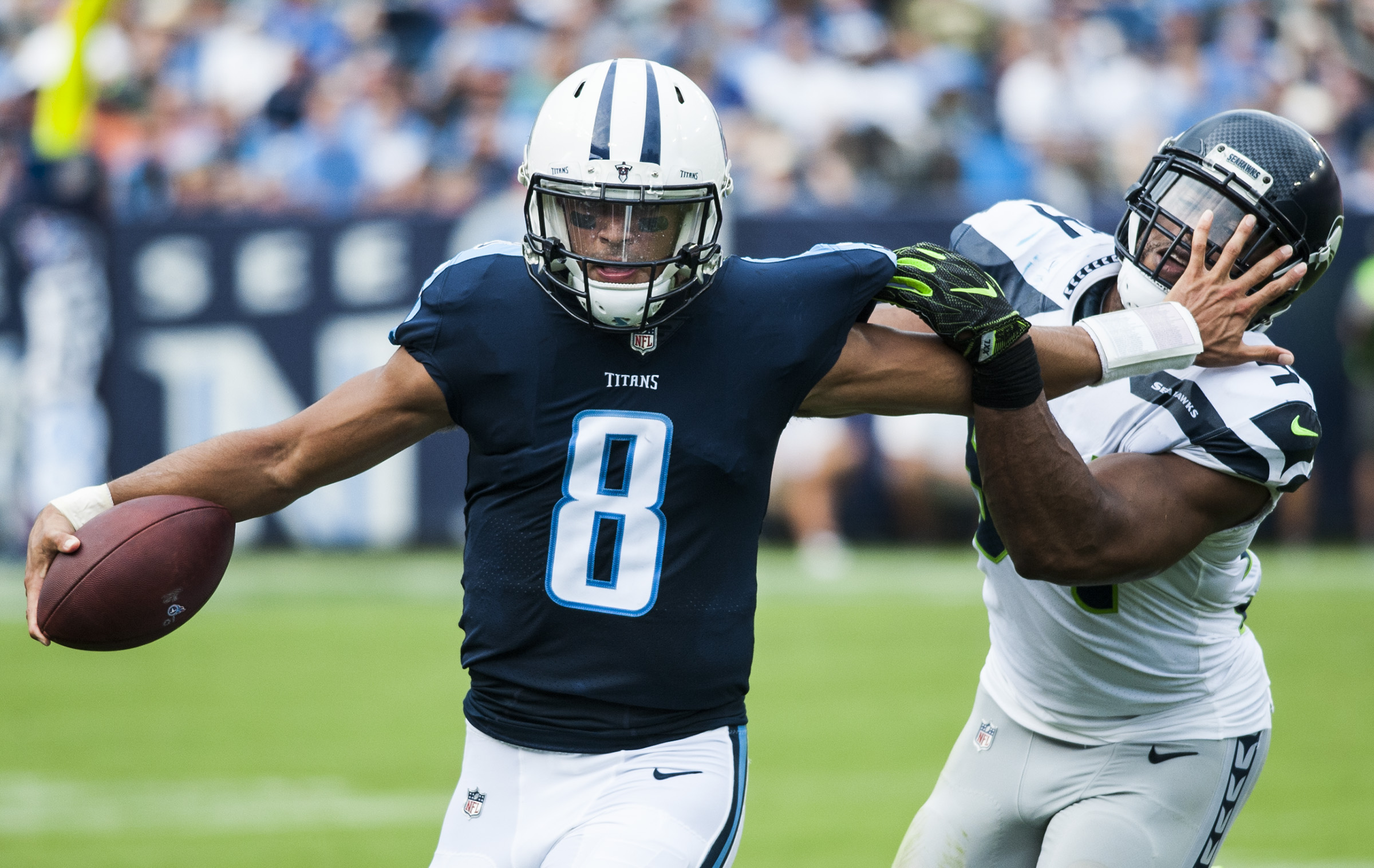 Tennessee Titans quarterback Marcus Mariota (8) stiff-arms Seattle Seahawks middle linebacker Bobby Wagner (54) as he runs out of bounds during the Titans' 33-27 win over Seattle on Sunday, Sept. 24, 2017, at Nissan Stadium.