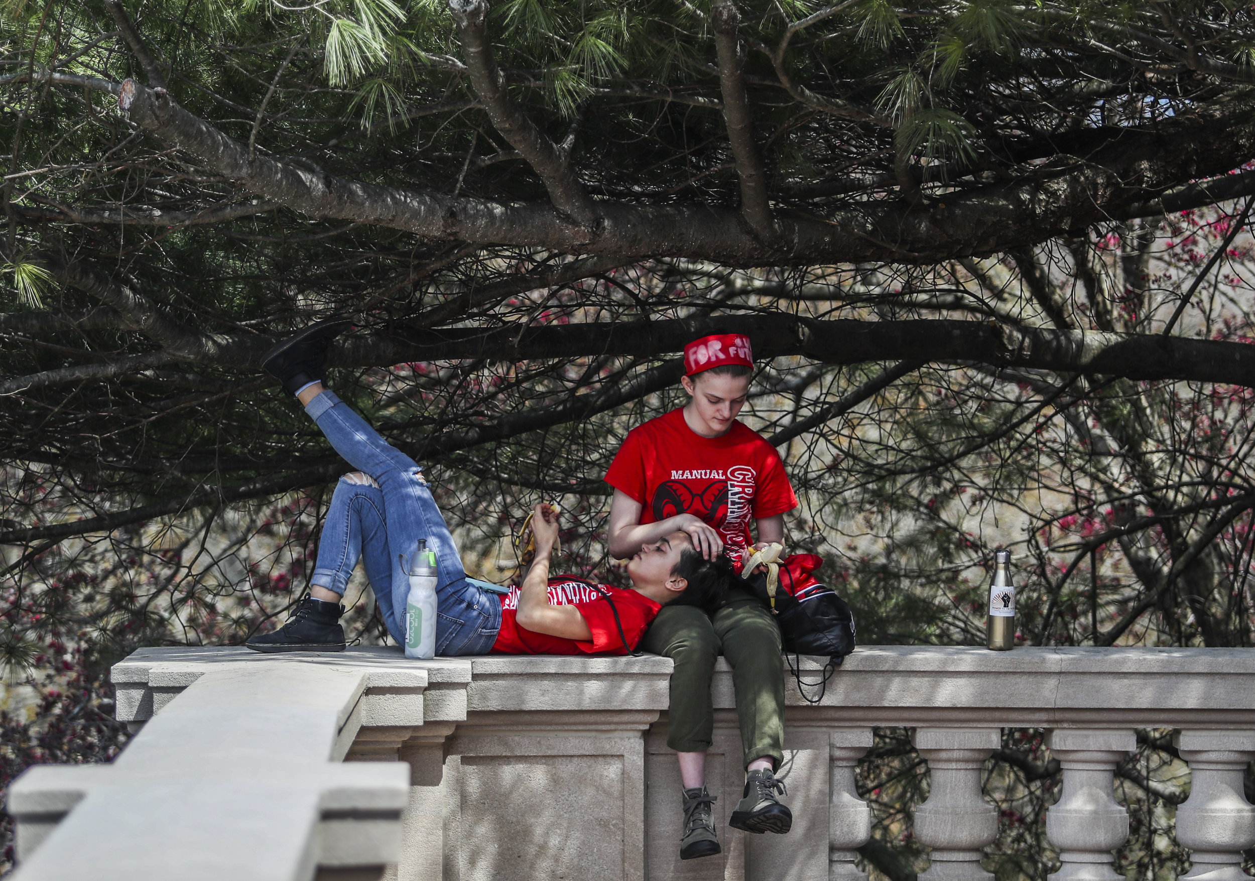Oli Tierney, left, and Sadie Lawrence, both sophomores at duPont Manual High School, take a break from protesting to sit in the shade on Friday, April 13, 2018, at the Kentucky State Capitol.