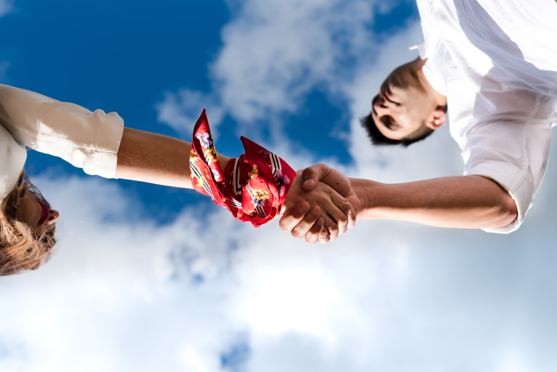 novios mano en la mano con lazo rojo y ciel nublado