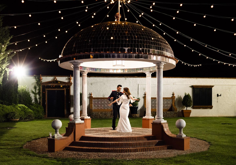novios bailando intimamente en el magico jardín iluminado de luces de la finca de la boda