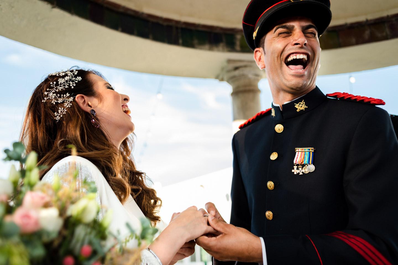 momento unico irrepetible de la ceremonia civil con traje militar y novios felices y sonrientes