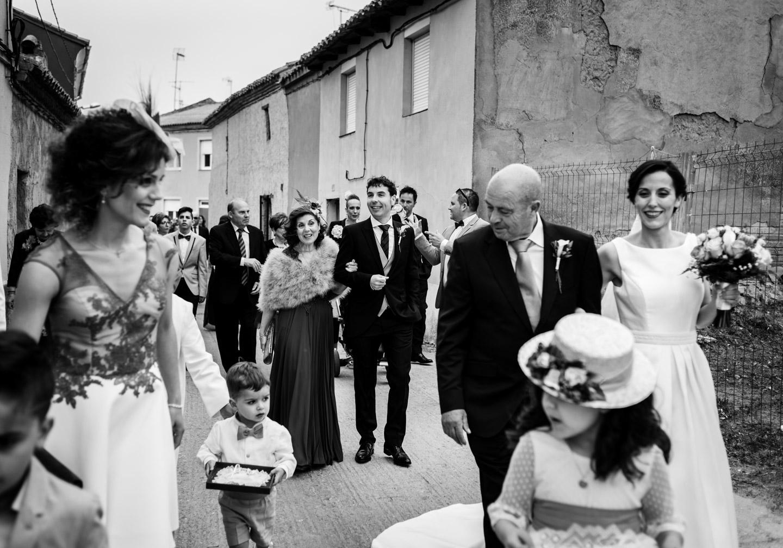 novios familia y invitados marchando todos juntos hacia la iglesia del pueblo
