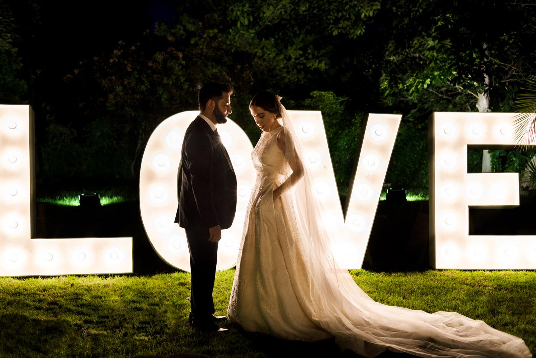 los novios posan delante de las letras LOVE de bombillas