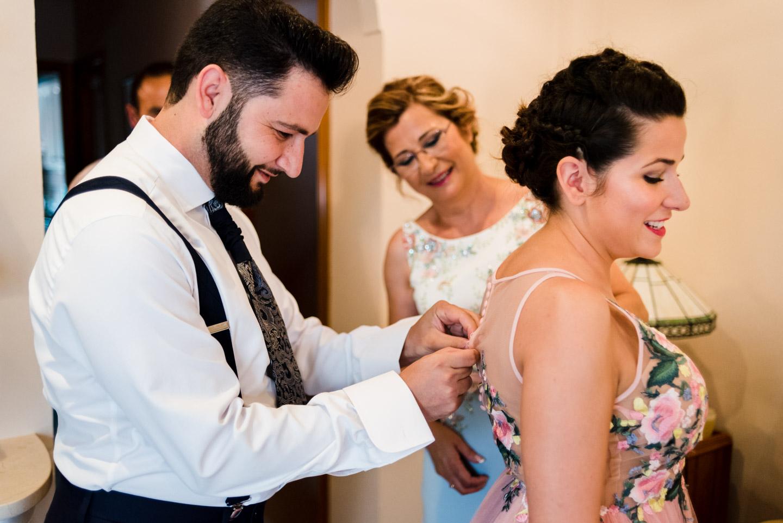 el novio ayuda su hermana abrocharse el vestido de la boda