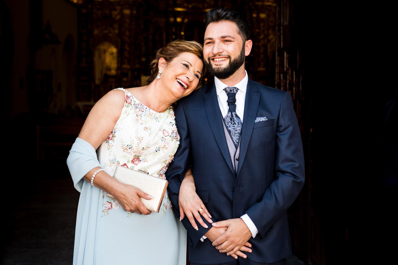 sonrisa tierna del novio con su madre a la entrada de la iglesia