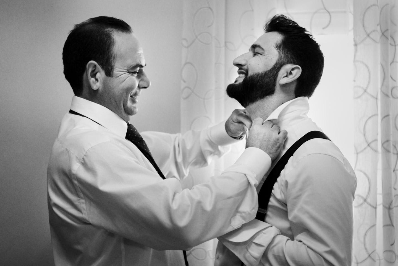 el padre del novio le ayuda a vestirse durante los preparativos