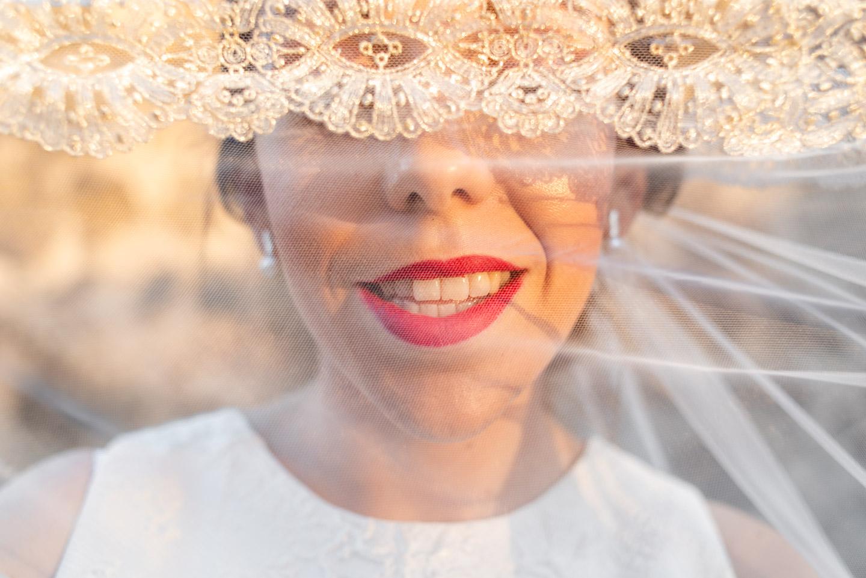 dettaglio della bocca della sposa con il velo del vestito