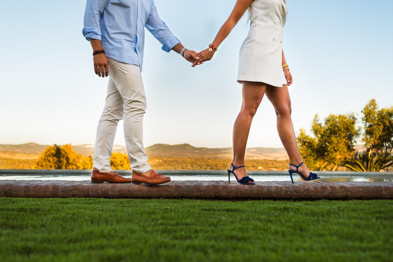 novios pasean mano en la mano al borde del agua