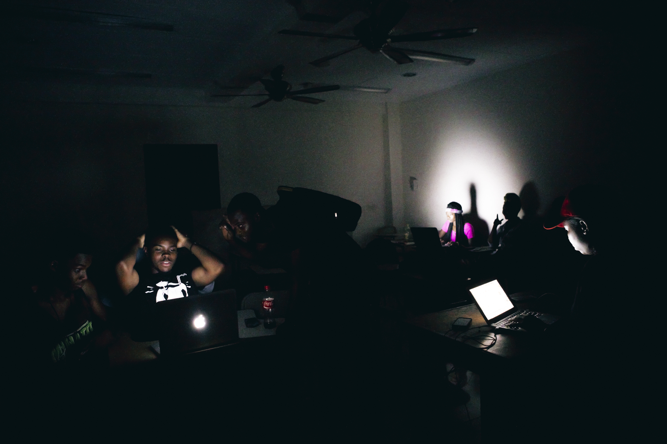 Students in a classroom at a University College in East Legon are working late on their laptops to meet deadlines, when a sudden power outage has them sitting in the dark.
