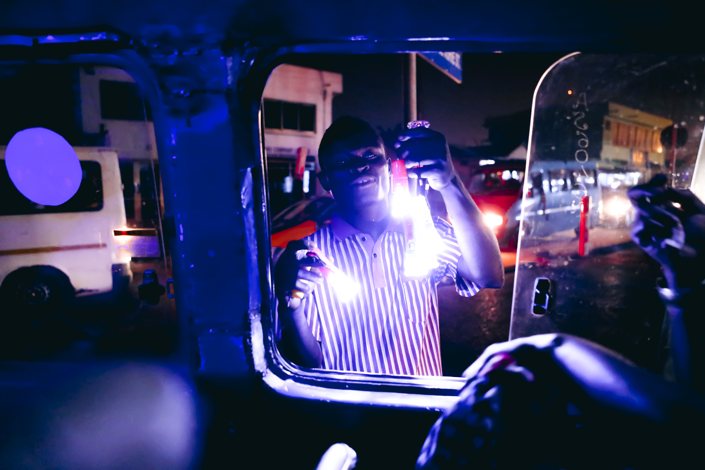 A man is selling a battery powered flashlight to a woman on her way home in a tro tro, in case the lights are out when she comes home. Tro tros are privately owned minibus share taxis.