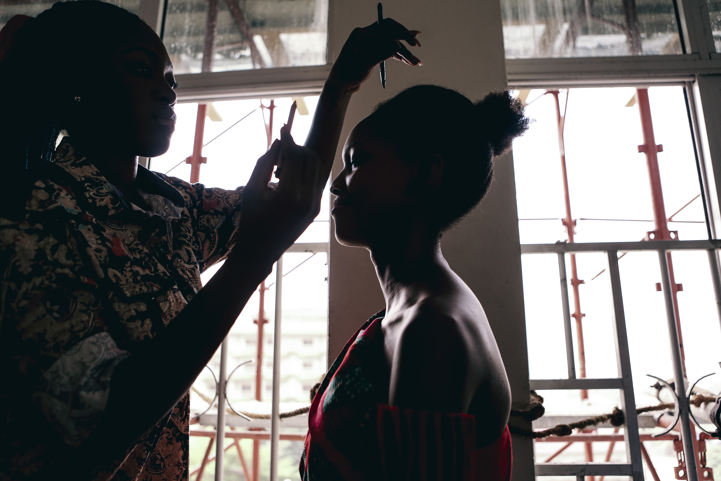 Since the lamps aren't working inside, a girl fixes her friend's make-up in the daylight coming from the window.