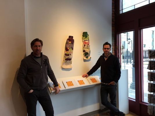 Gallery owner, Anthony Brunelli, with gallery director, John Brunelli, pose in front hyperrealistic paint tubes by artist Ray Gross