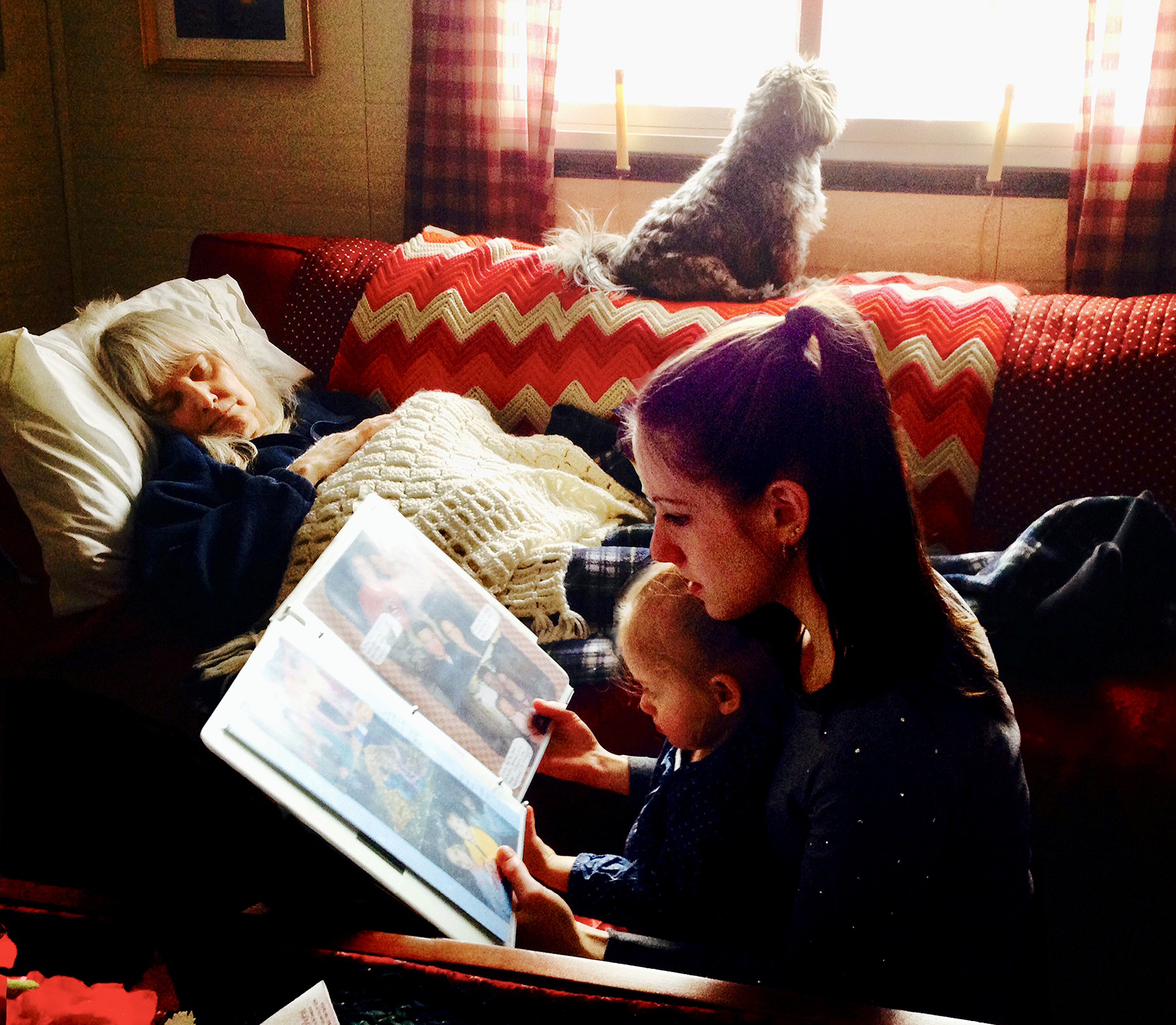 My daughter Mackenzie, and granddaughter Mia looking at scrapbooks by my mother's bedside.