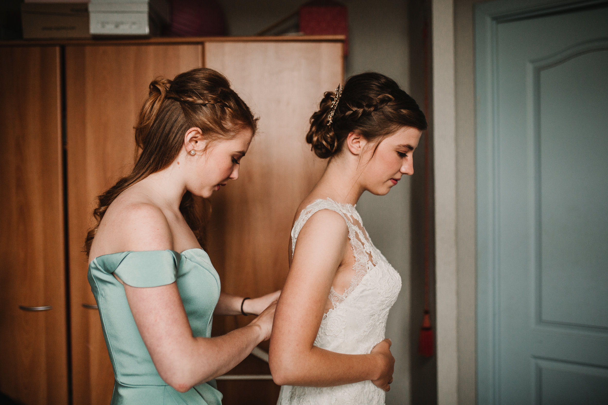 Bridesmaid helping bride into dress before city hall ceremony in Ghent, Belgium