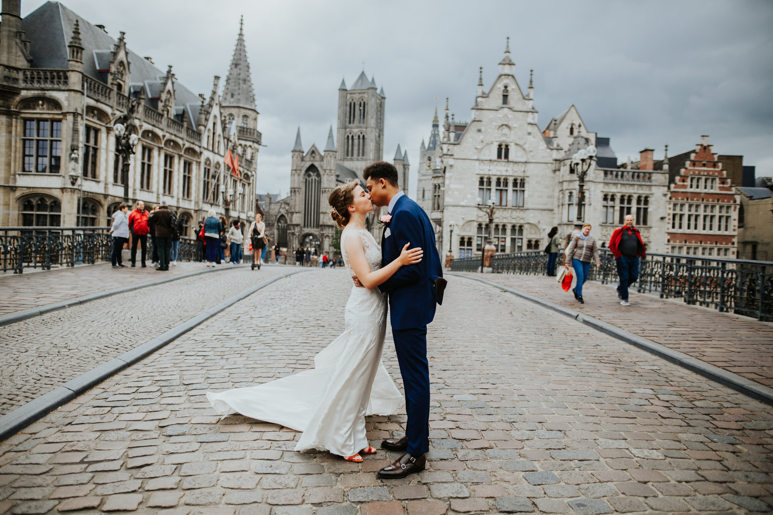 Couple kissing on bridge overlooking the old cityscape of Ghent, Belgium