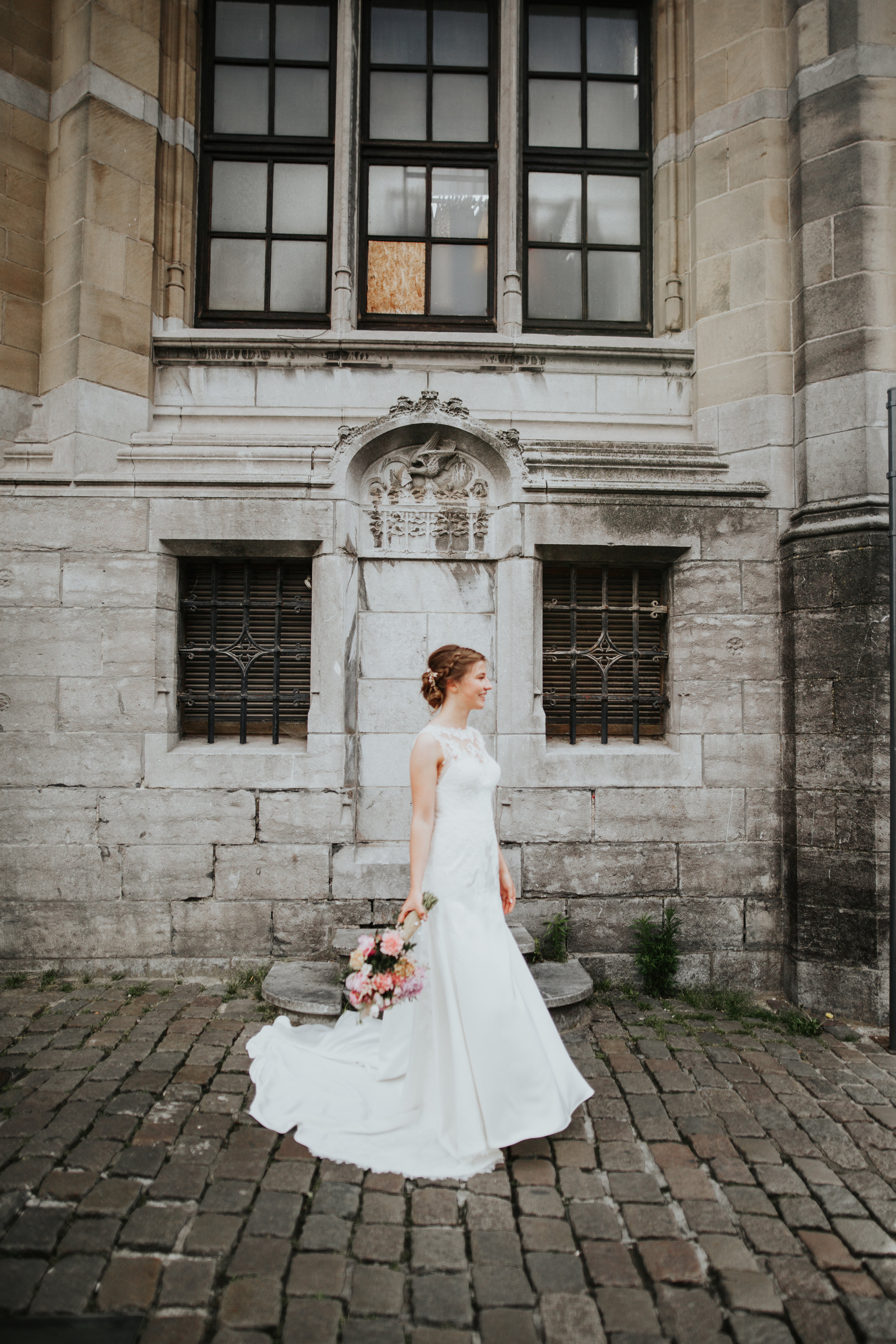 Bride smiling in windswept dress outside the old Post Office building in Ghent, Belgium